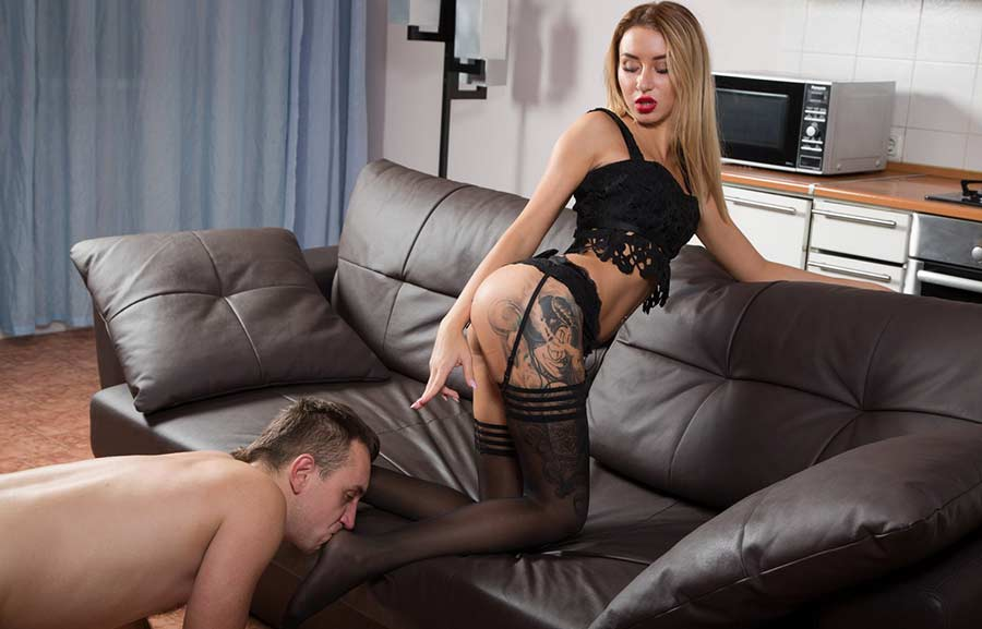 Dominatrix showing slave to lick her feet in nylons