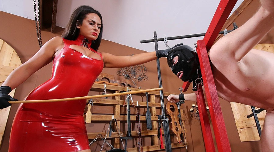 red PVC dominatrix with a cane